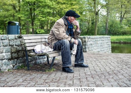 Smoking Homeless Man Sitting On Bench In Park.