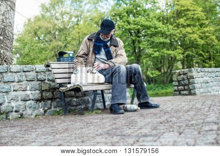 Homeless Man Searches Bag On Bench In Park.