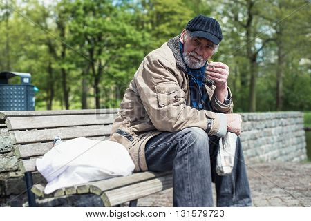 Homeless Man Smoking Cigarette On Bench In Park.