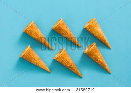 Empty ice cream cornets on blue background