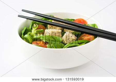 Vegan tofu salad with tomatoes and lamb's lettuce isolated on white background