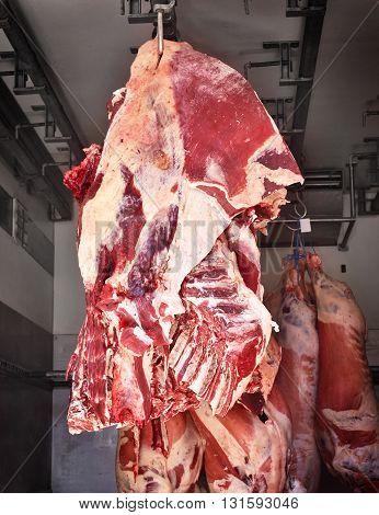 Raw beef, butchery transport. Raw meat hanging on meat hooks in a truck. Meat transportation.