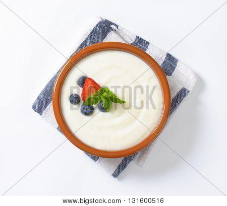 bowl of semolina pudding with fresh fruit on striped napkin