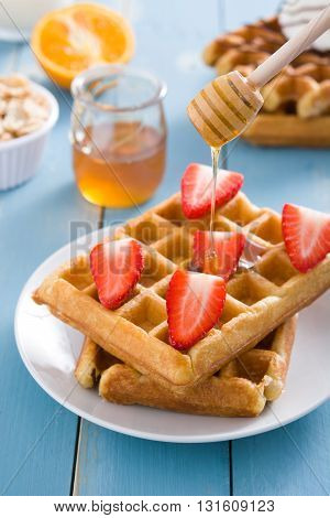 Waffles with strawberries and honey on blue wood