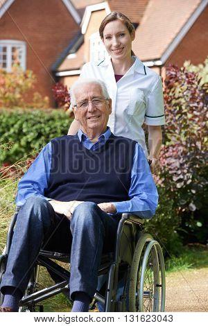 Portrait Of Carer Pushing Senior Man In Wheelchair
