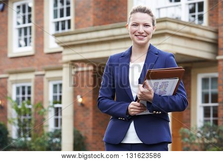 Portrait Of Female Realtor Standing Outside Residential Property