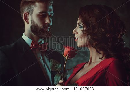 Young elegant couple. Woman in red holding rose and looking on man. Focus on woman. Vintage film style colors.