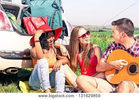 Multiethnic friends playing guitar sitting behind car on road trip - Multicultural teenagers having fun listening guitarist during spring break holiday - Concept of country style camping vacation and freedom