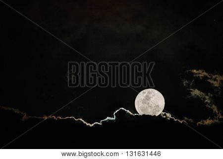 Full moon rising through the clouds at night