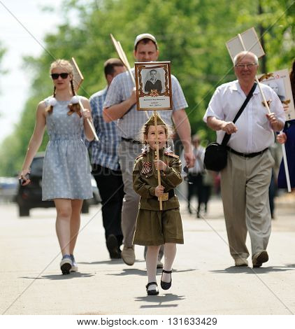 Orel Russia - May 9 2016: Celebration of 71th anniversary of the Victory Day (WWII). Girl with poster her great-grandfather on Immortal regiment marching closeup