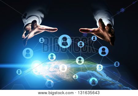 Global social networking with businessman hands grabbing globe with connected icons.