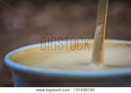 Coffee latte in the paper cup with wooden mixing stick