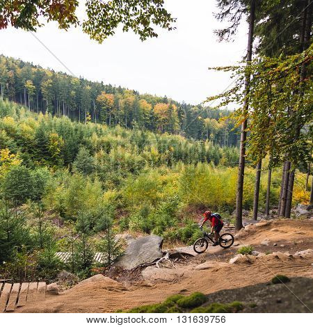 Mountain biker riding on bike in autumn inspirational mountains landscape. Man cycling MTB on enduro trail path. Sport fitness motivation and inspiration. Rider mountain biking in fall woods.