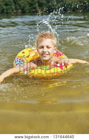 Boy with floating ring splashing wather in the lake and learning how to swim