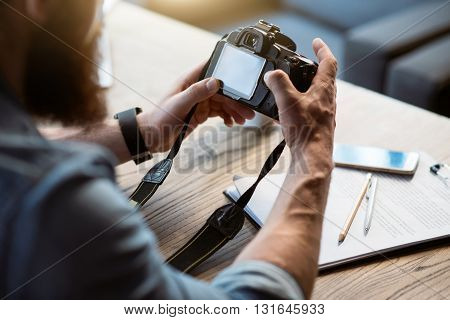 Real photographer. Pleasant bearded man sitting at the table and holding photo camera