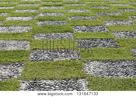 Alternating pattern of green grass and grey stones