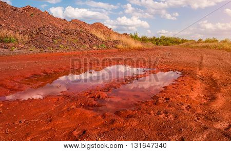 puddle in trail on red ground in Krivyi Rih, Ukraine