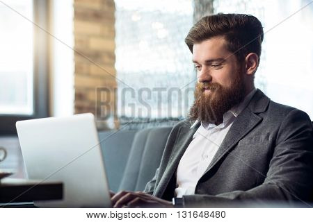 Share positivity. Pleasant cheerful delighted bearded man smiling and using  laptop while expressing gladness