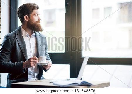 Live with pleasure. Cheerful delighted bearded man holding cup and looking in the window while standing in the office