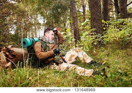 Soldier in camouflage relaxing in a forest.