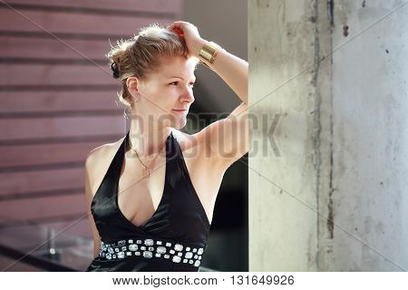 Blonde caucasian woman in black dress portrait.