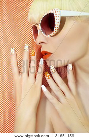 Sunny orange manicure with dots on the women's nails and makeup closeup in sunglasses.