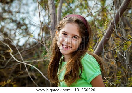 Natural light portrait of a snaggle tooth girl sitting in a desert tree.
