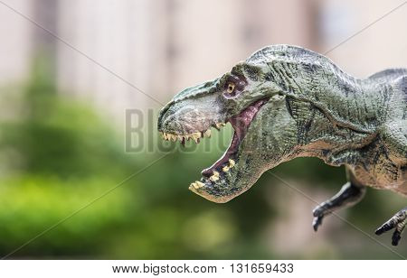 tyrannosaurus toy in front of trees and a morden building