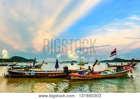 Rawai Thailand - August 17 2014: Traditional long-tail boats & speed boats used for tourist trips & fishing moored in bay at sunset off Rawai beach on southern tip of Phuket southern Thailand