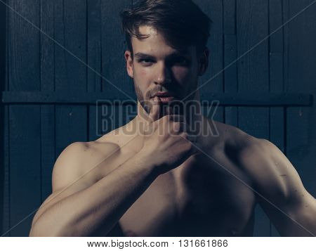 Young man with muscular bare chest and sexy body posing in studio on wooden background