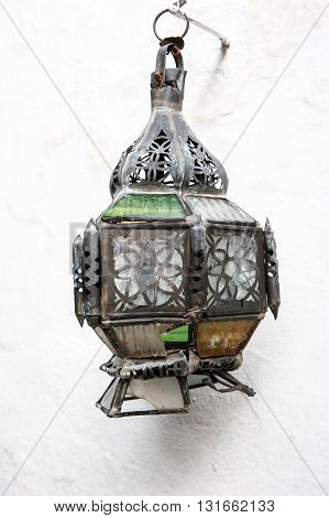 Old broken lamp hanged on white wall in Fez, Morocco