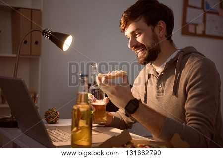 Nice conversation. Contended young guy holding a slice of pizza and drinking a beverage while chatting on the laptop in the evening