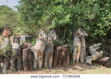 Chettinad India - October 16 2013: Ayyanar village protector Horse shrine of Namunasamudran. Line of clay horses in different stages of deterioration.