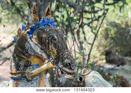 Chettinad India - October 16 2013: Ayyanar village protector Horse shrine of Namunasamudran. Blue crowned head of horse blackened by mold.