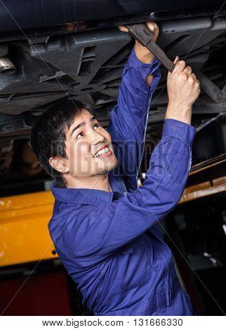 Happy Mechanic Working Underneath Car