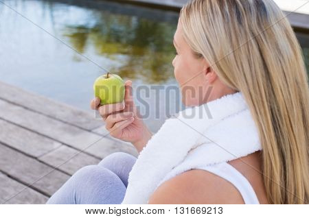 Healthy mature woman eating green apple after exercising. Rear view of senior woman eating an apple after morning workout routine. Back view of blond woman having healthy fruit after yoga.