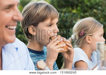 Happy boy eating hamburger with his family. Young boy having lunch with sandwich. Portrait of a child eating at family party.