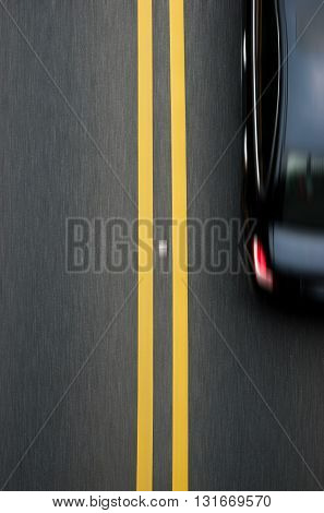 double yellow lines divider on blacktop with a car passing