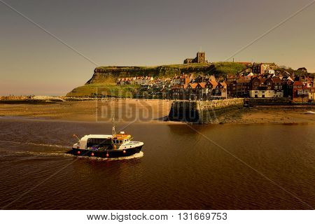Fishing boat returns to harbour sailing up River Esk, Whitby, North Yorkshire. Warm filter added.
