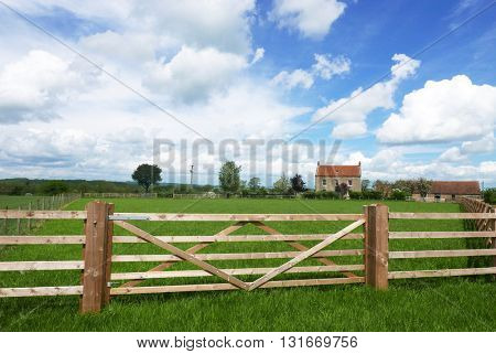 Farmers fence surrounds grass area with farm in background