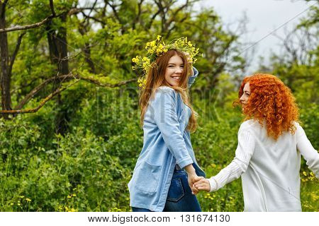 Best friends forever. Girlfriends strolling hand in hand. BFF. Walk. The girl on a head a wreath of wildflowers.