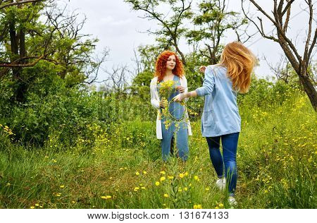 Best friends forever. Friends meet in the park. BFF. A girl holding a bouquet of wildflowers. A friend runs to meet.