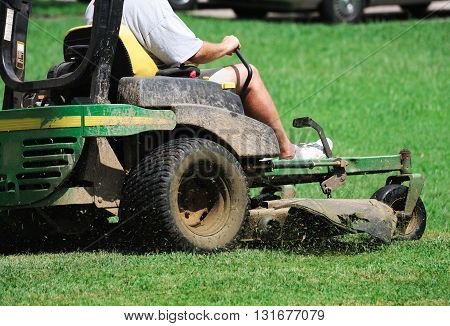 close up on outdoor worker mowing the lawn