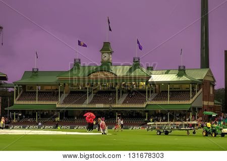 SCG SYDNEY NSW/AU JAN 26 2015 - India Vs South Africa Cricket rainwashed Match. Umpires trying desperately to have some game on pitch cover ready to be removedstill few people staying around in the members pavillion. The sky turned amazingly purple.