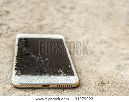 Close up of broken mobile phone drop on cement floor with copy space High Key Shallow Depth of Field