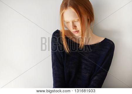 Attractive Teenager Model Wearing Stylish Black Top Looking Down With Shy And Dreamy Expression On H