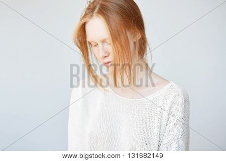 Beautiful Female Teenage Model Wearing Casual White Top Looking Down With Shy And Thoughtful Express