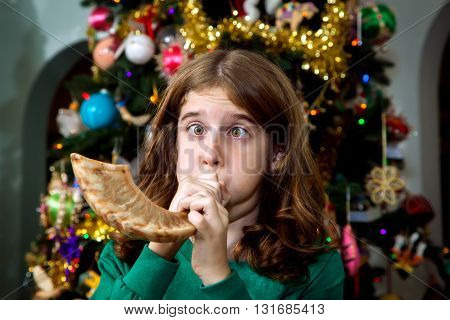 A young Christian girl blows a Jewish Shofar on Christmas morning. It's a melding of religions and traditions as she stands in front of a Christmas tree. She is blowing so far that her cheeks are puffed out and her eyes are slightly crossed.