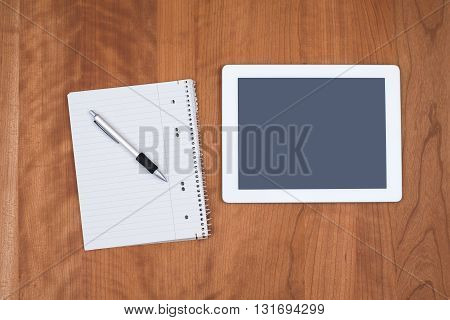 tablet PC and notepad with pen on wooden table from above