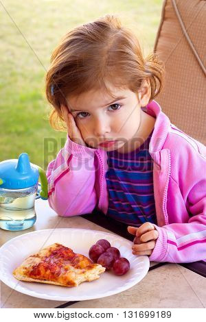 A toddler girl sits pouting and glaring in front of a plate of partially eaten food.